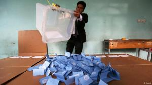 An election helper empties a ballot box after the Afghan presidential election (photo: Reuters)