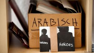 "Postcards advertising the Berlin ""Heroes"" project in front of a cardboard box marked ""Arabic"" (photo: picture-alliance/dpa)"