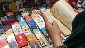 An Iranian woman reading a book in front of a book display in Tehran (photo Shabestan.ir)