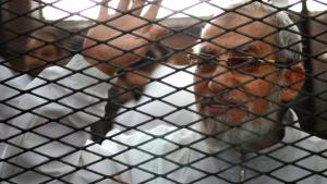 Mohammed Badie, the spiritual leader of the Muslim Brotherhood in Egypt, waves from inside the defendants' cage during the trial of brotherhood members in February 2014 (photo: Ahmed Gamil/AFP/Getty Images)