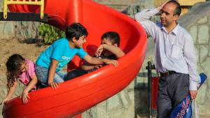 An Iranian father with his three children at a playground in Tehran (photo: ISNA)