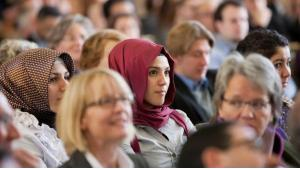 Two Muslim students in headscarves in the audience at a public event at a university. Photo: dpa