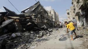 A Palestinian boy sweeping up rubble outside a bombed-out building in Gaza (photo: AFP/Getty Images)