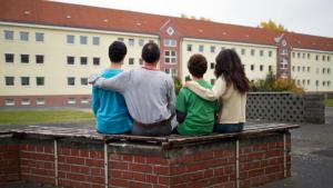 A Syrian family sitting outside a home for asylum seekers run by the Central Authority for Foreign Residents in the German state of Brandenburg (photo: dpa/picture-alliance)