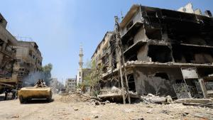 Forces loyal to Syria's President Bashar al-Assad drive a tank past damaged buildings in Mleiha, Syria, 15 August 2014 (photo: Reuters)