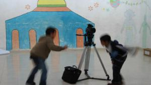 Two Palestinian boys on a film set with a camera (photo: Palestinian Social Cinema Arts Association)