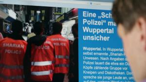 """A man reads an Internet report about the """"Sharia police"""" in Wuppertal on 5 September 2014 (photo: Oliver Berg/dpa)"""