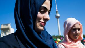 "Two Muslim women pass the event ""About Berlin - religions make history"" in Berlin (photo: Carsten Koall/Getty Images)"