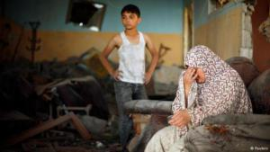 A Palestinian woman and boy in the ruins of their home (photo: Reuters)