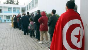 A man draped in a Tunisian flag stands at the back of a queue (photo: picture-alliance/dpa)