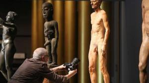 "A photographer takes a close up of one of the figures at the exhibition ""SNIP IT! Stances on Ritual Circumcision"" at the Jewish Museum in Berlin (photo: dpa/Wolfgang Kumm)"