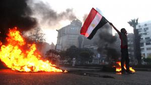 A supporter of Egypt's ousted President Mohammed Morsi holds a national flag as he stands next to burning tyres during a protest in Cairo, 30 August 2013 (photo: AP Photo/Khalil Hamra)