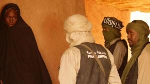 "A woman in a chador faces three jihadis (scene from Abderrahmane Sissako's film ""Timbuktu"")"