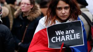 """A woman wearing a French tricolour holds a 'We are Charlie' sign during a march for the victims of the """"Charlie Hebdo"""" shootings in Paris, Liverpool, England, 11 January 2015 (photo: Reuters/Noble)"""