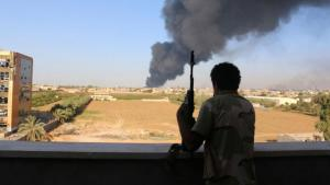 A fighter from Zintan brigade watches as smoke rises after rockets fired by one of Libya's militias struck and ignited a fuel tank, Tripoli, 2 August 2014 (photo: Reuters)