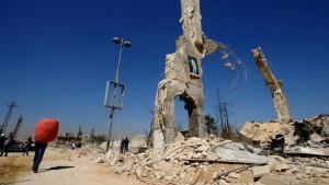 A photo of Syrian President Bashar al-Assad hangs on a ruined building in Al-Dukhaneya on the outskirts of Damascus (photo: Reuters/Omar Sanadiki)