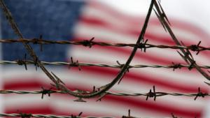 Barbed wire in front of an American flag (photo: picture-alliance/AP Photo/B.Linsley)