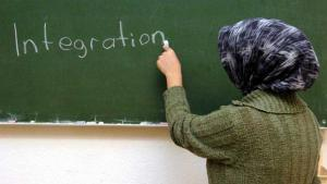 A woman in a headscarf writes the word integration on a chalk board (photo: dpa/picture-alliance)