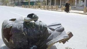 A sandal rests on the head of a demolished statue of Saddam Hussein in Baghdad (photo: AP)