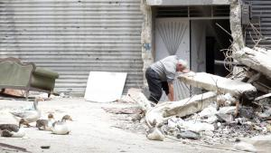 A man sifting through rubble on a street in the Yarmouk Palestinian refugee camp south of Damascus, Syria (photo: picture-alliance/epa/Y. Badawi)