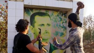 Syrian opposition fighters get ready to destroy a poster of President Bashar al-Assad, early June 2015 (photo: DW/AA/I. Hariri)