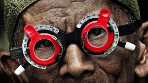 "Inong with red optometry glasses on the film poster for ""The Look of Silence"" (photo: Dogfoof)"