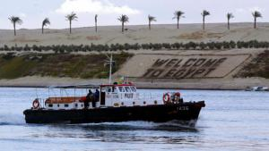 "A pilot boat passes a huge ""Welcome to Egypt"" sign on the new section of the Suez Canal (photo: picture-alliance/dpa/M. Nelson)"
