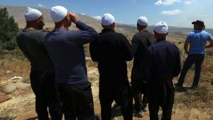 Druze men residing in Israel watching smoke rise from the Syrian Druze village of Hader, 16 June 2015 (photo: JALAA MAREY/AFP/Getty Images)