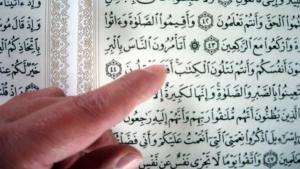 Finger pointing at a page of the Koran (photo: Ulrike Hummel)
