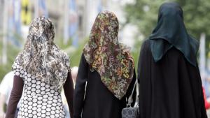 Three young women wearing headscarves walk through the city centre of Munich (photo: dpa/picture-alliance)
