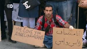 A Syrian refugee in Berlin with an Angela Merkel placard (photo: DW/S. Amri)