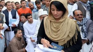 An Afghan woman holds her new passport at the passport office in Kabul (photo: picture-alliance/dpa/S. Bandari)