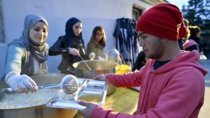 Mosque congregation member distributes food to refugees (photo: picture-alliance/dpa/H. Neubauer)