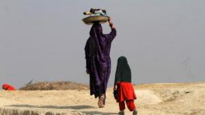 Pakistani woman carrying laundry back home (photo: Reuters/Fayaz Aziz)