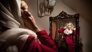 1.	A scarf over blonde hair, a coat over Western clothing: an Iranian woman preparing to leave the house. The beauty ideals in Iran are a tightrope walk between traditional and modern, explains photographer Samaneh Khosravi. Many Iranian women emulate the appearance of Hollywood actresses, following them via the Internet or satellite TV