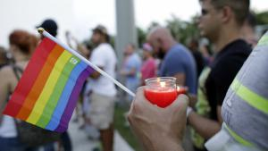 A man holds a candle and a rainbow flag during a vigil in memory of the victims of the Orlando mass shooting (photo: picture-alliance/AP Photo/L. Sladky)