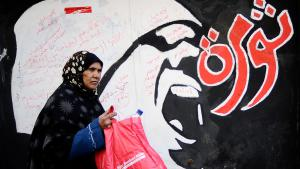 A woman passes revolution graffiti in Cairo (photo: Getty Images/AFP/F. Monteforte)