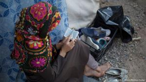 Month of prayer: sitting next to her family′s tent, Farida from Afghanistan reads a tiny Koran in the hours before the iftar meal, when Muslims break the daytime fast. During the month of Ramadan, most Muslims forego food and water during daylight hours and feast at nightfall