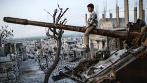 Boy sits on a wrecked tank in Kobani (photo: Getty Images/AFP/Y. Akgul)