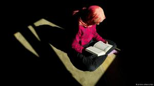 A Muslim woman studies the Koran