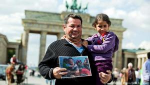 Iraqi refugee Laith Majid Al-Amirij with his daughter Noor in front of the Brandenburg Gate (photo: picture-alliance/dpa/J. Carstensen)