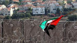 Palestinian flag caught in barbed wire in front of the wall protecting illegal Israeli settlements