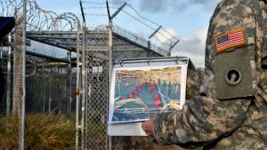 U.S. soldier displays a photo of the infamous ″Camp X-Ray″ in front of Guantanamo Bay detention camp (photo: Getty Images/AFP/M. Antonov)