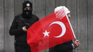 A man bearing the Turkish flag walks past a Turkish police office guarding the Reina nightclub in Istanbul following the New Year's Eve terrorist attack (photo: picture-alliance/AP Photo/E. Gurel)