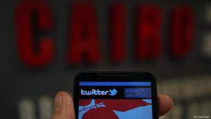 Smartphone with Twitter logo in front of the word 'Cairo'