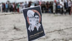 Demonstration poster caught on a barbed wire fence showing Shia cleric Sheikh Isa Ahmed Qassim and murdered teenager Mustafa Hamdan (photo: picture-alliance/NurPhotos/A. B. Al Kamel)