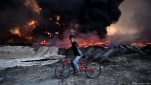Iraqi boy riding past a burning oil-field following an IS attack in Qayyarah near Mosul (photo: Getty Images/C. Court)
