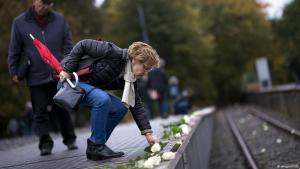 Woman places white roses at the platform 17 memorial to Holocaust victims, Grunewald station, Berlin (photo: imago/IPON)