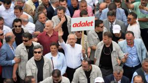 """Kemal Kilicdaroglu holds up an """"Adalet"""" (Justice) placard during the March for Justice (photo: Reuters)"""