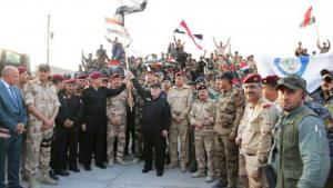 Iraqi Prime Minister Haider al-Abadi (centre) holds an Iraqi flag as he announces victory over Islamic State in Mosul, Iraq, 10 July 2017 (Reuters)